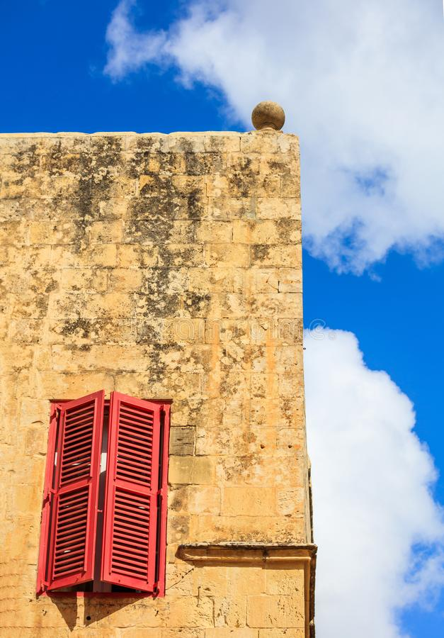 Malta, Mdina. Red window on a yellow sandstone wall in the old medieval city. Blue sky background stock images