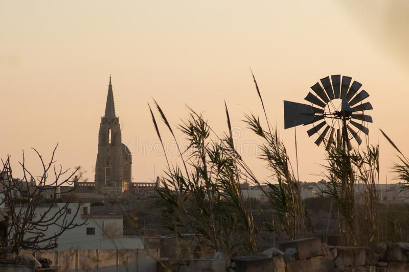 Windmill sunset in Malta seaside. Malta sunset with the chapel and windmill popping up in the distance stock photo