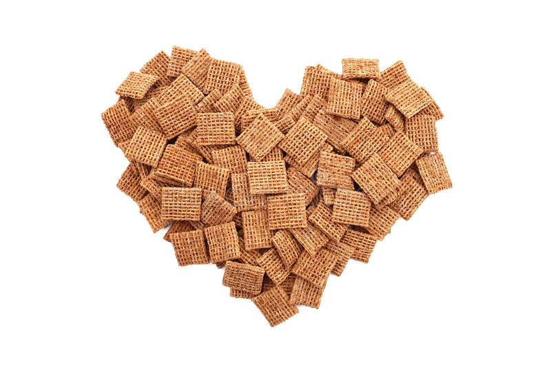 Malted wheat biscuits breakfast cereal heart. Malted wheat biscuits breakfast cereal in a heart shape, isolated on a white background stock image