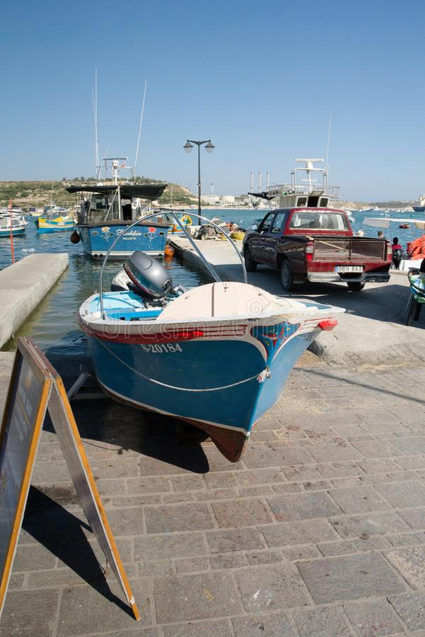 Marsaxlokk, Malta, August 2019. A fishing boat on the shore next to a red car. royalty free stock images