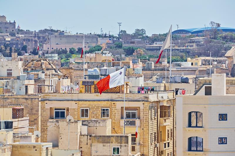 Maltese white - red flag against typical malta residential buildings. In sunny summer day stock photo