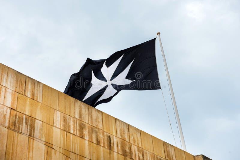 Malteser Kreuz auf einer Flagge lizenzfreie stockbilder