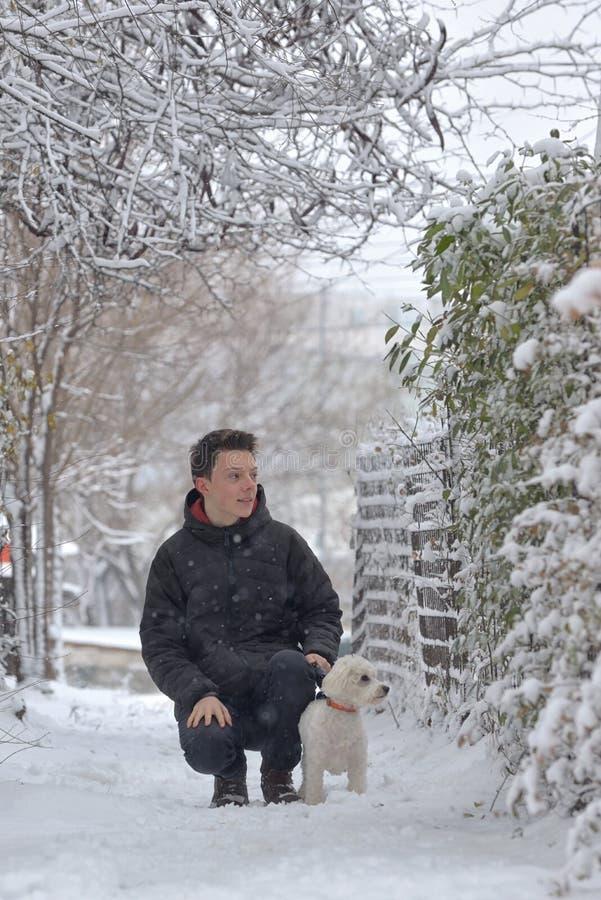 Maltesisk hund och tonårig pojke på vinter arkivbilder
