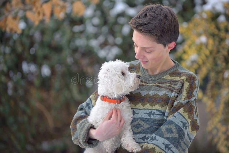 Maltesisk hund och tonårig pojke på vinter arkivfoton