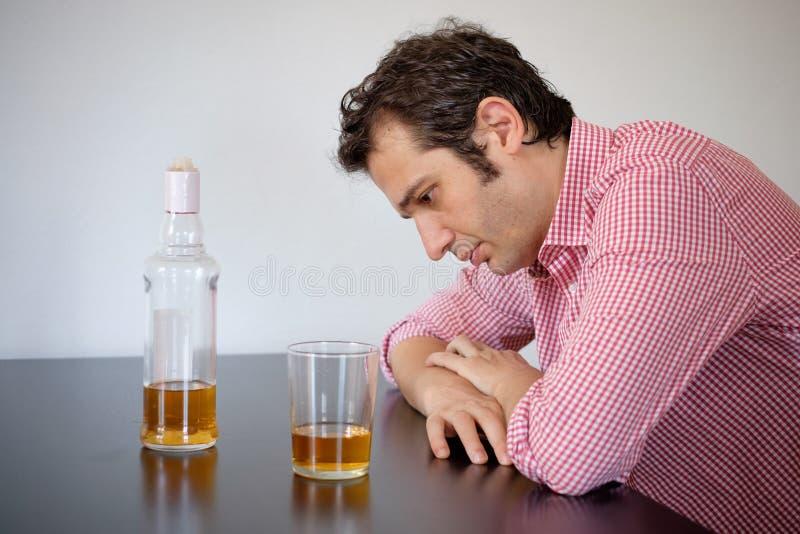 Maltraiter d'homme de l'alcool se sentant triste image libre de droits