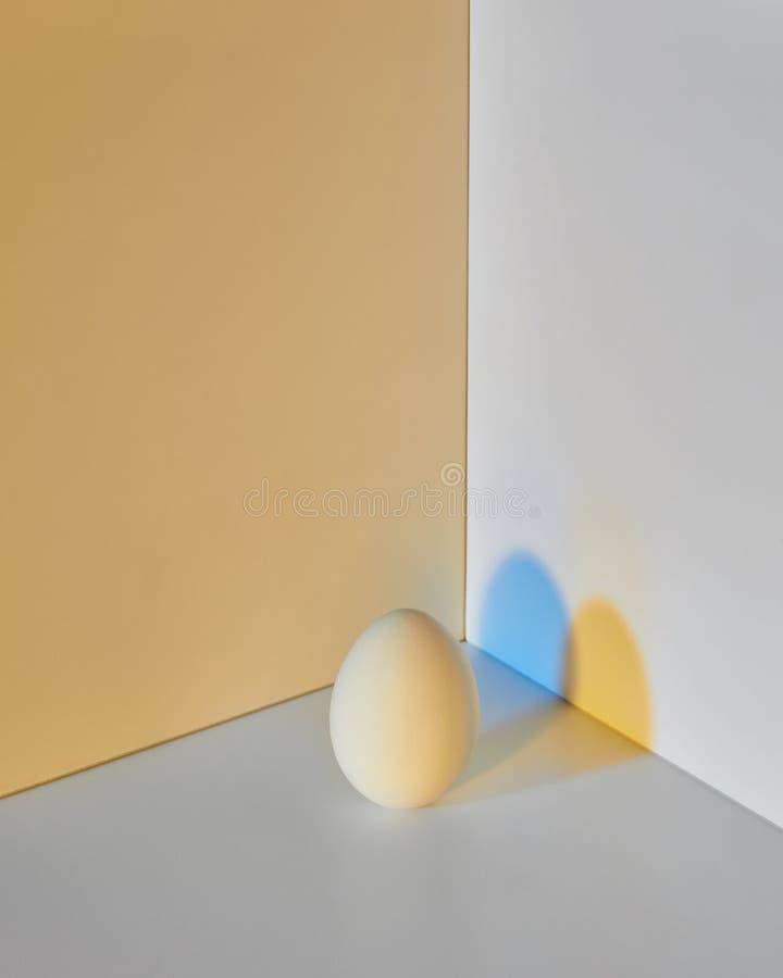 Malujący jajko na kolor żółty kopii tle z odbiciem kolorów żółtych cienie i kopii przestrzeń dla teksta Wielkanoc fotografia royalty free
