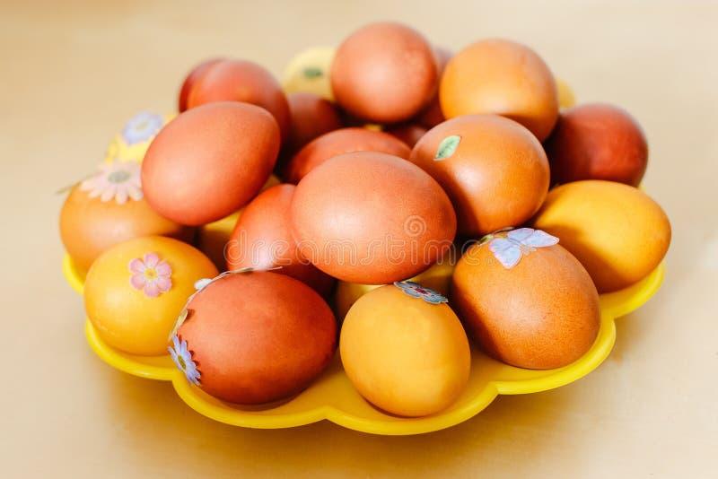 Malujący z naturalnego barwidła Wielkanocnymi jajkami na talerzu obraz stock