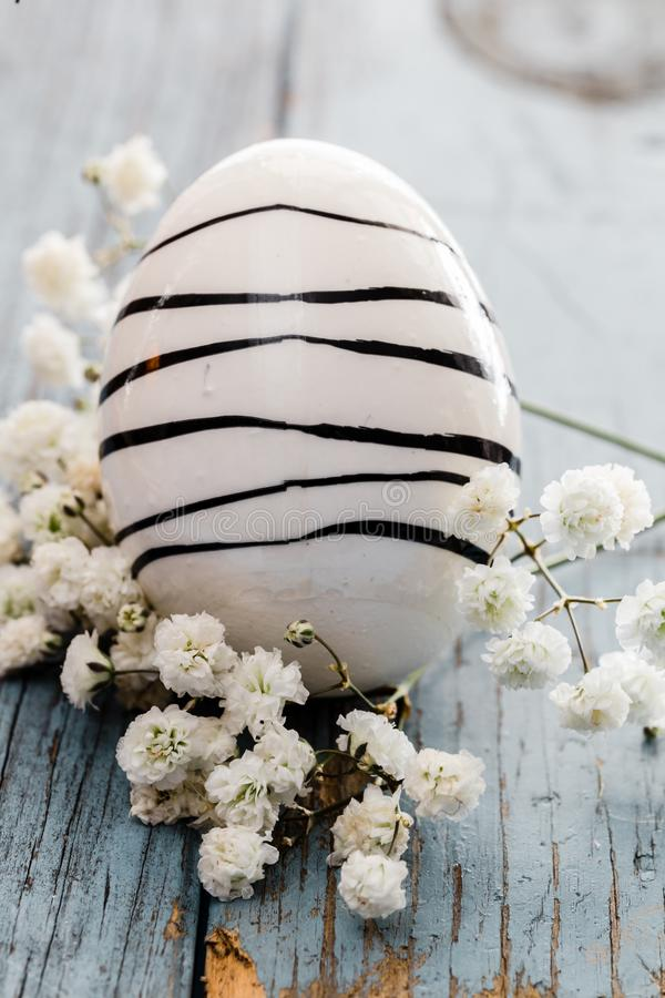 Malujący Easter jajko z czerń lampasami na błękitnym drewnianym stole z białymi kwiatami i zdjęcia royalty free