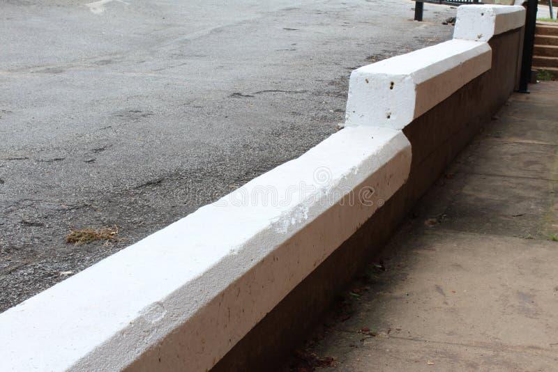 Malujący gęsty bielu betonu krawężnik między podwyższoną drogą i chodniczkiem zdjęcia stock