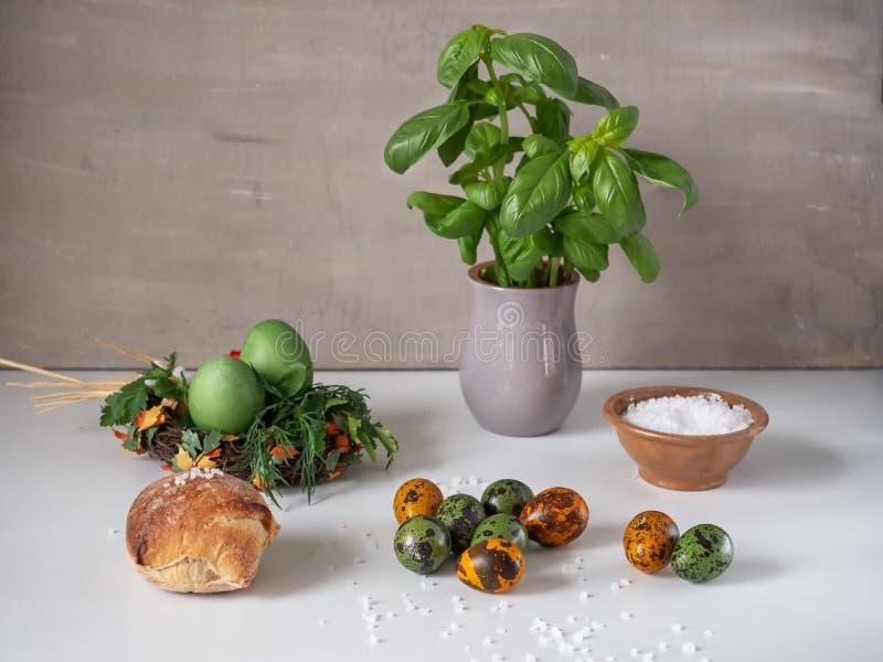 Malujący jajka zieleń i zmrok kurczaka i przepiórki - pomarańcze na białym stole Świeży basil w glinianym szarość garnku zdjęcie stock