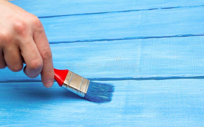 Malujący na drewnie, ręka z muśnięciem, błękitny drewno zdjęcie royalty free