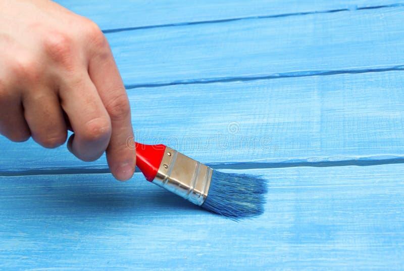 Malujący na drewnie, ręka z muśnięciem, błękitny drewno zdjęcia royalty free