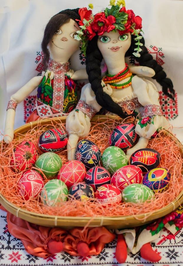 Malujący Wielkanocni jajka w koszu z tradycyjnymi lalami obraz royalty free