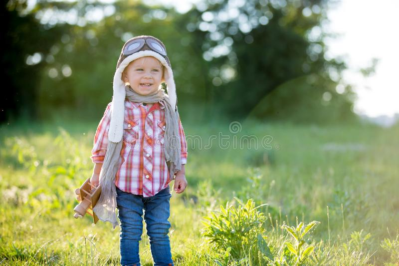 Malutki chłopczyk, dziecko bawiące się samolotem w polu maku, piękny zachód słońca fotografia stock