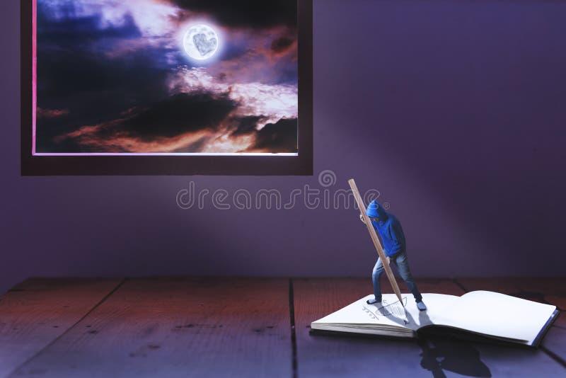 Malutki mężczyzna writing serce na książce wśród światła księżyc w pełni obraz royalty free