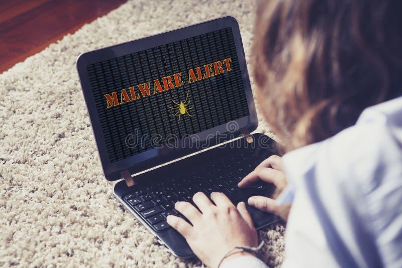 malware戒备惊奇的妇女,当使用便携式计算机时 免版税库存图片