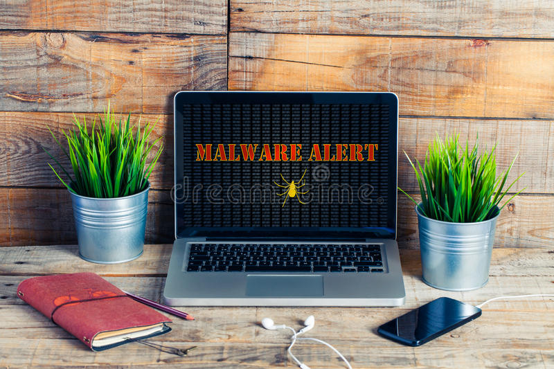 Malware alert in a laptop computer screen at the office. stock photo
