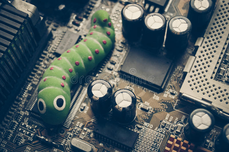 Malware. Worm on computer circuit board / computer security breach due to worm attack royalty free stock photography