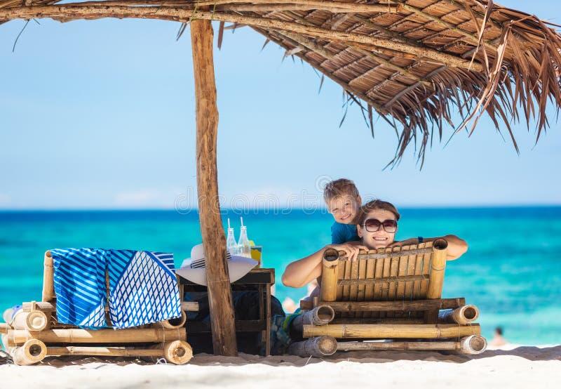 Mamá alegre e hijo que disfrutan de día hermoso en la playa imágenes de archivo libres de regalías