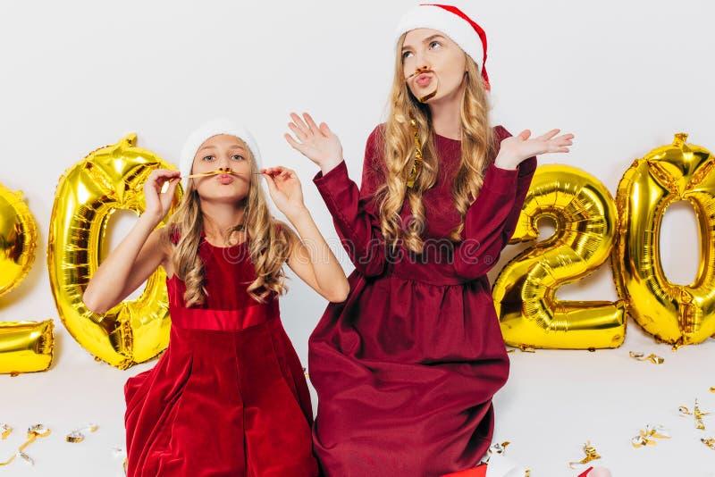 Mamá alegre y su linda hija con sombreros de Santa. Un padre y un niño pequeños se divierten con regalos de Navidad en un fondo imagenes de archivo