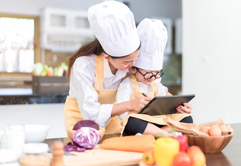 Mamá asiática del cocinero profesional que enseña a poco cocinar del menú de la lista del hijo foto de archivo libre de regalías