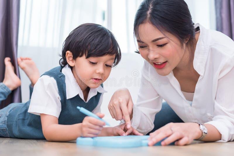 Mamá asiática que enseña al muchacho lindo a dibujar el corazón rojo en tablero con la pluma del color De nuevo a escuela y a con imágenes de archivo libres de regalías