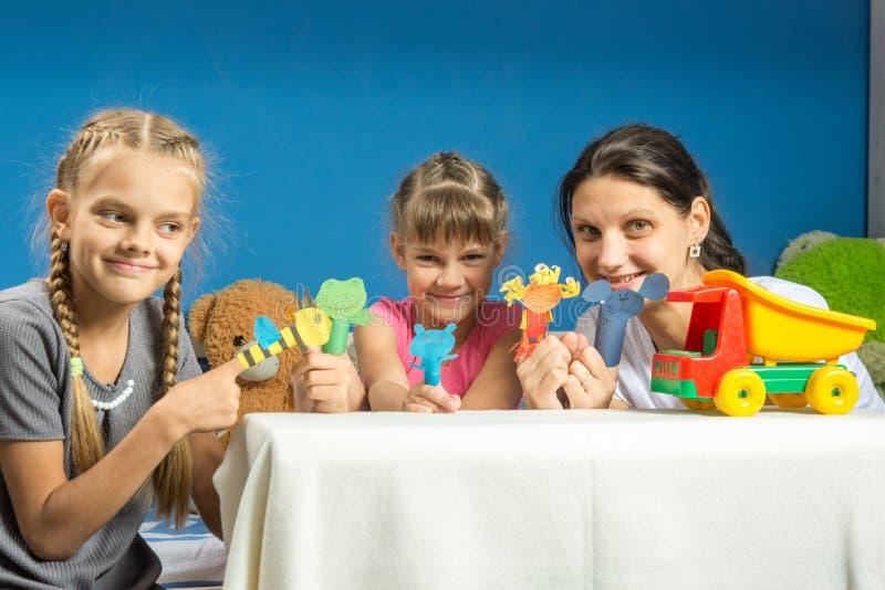 Mamá con dos hijas que juegan en teatro de expediente de la marioneta del finger imágenes de archivo libres de regalías