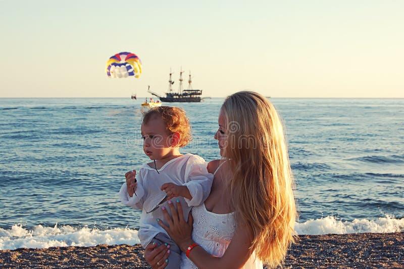 Mamá con el bebé en la playa en el lado, Turquía imagen de archivo libre de regalías