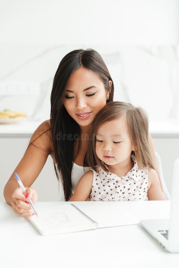 Mamá con la pequeña muchacha asiática linda que usa notas de la escritura del ordenador portátil imagen de archivo libre de regalías