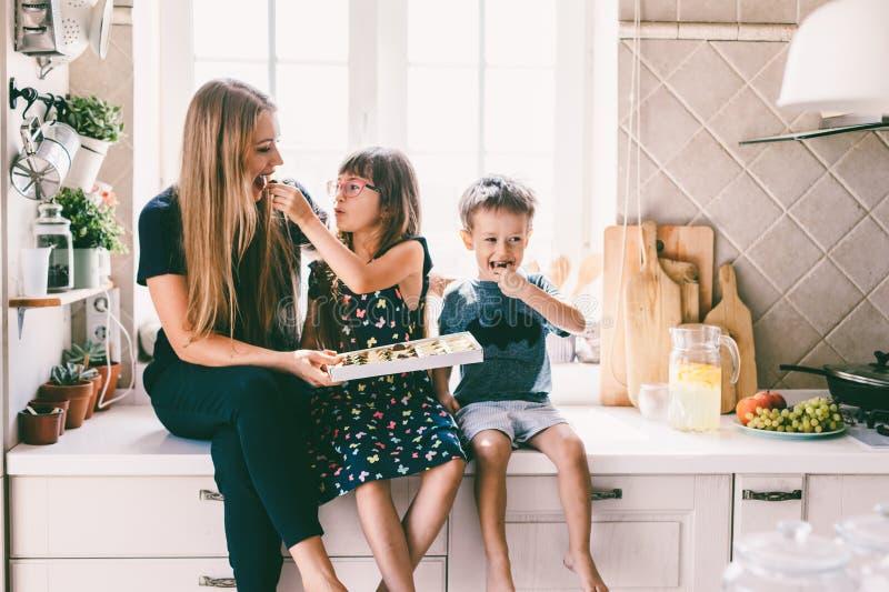 Mamá con los niños que comen en la tabla de cocina imagen de archivo libre de regalías