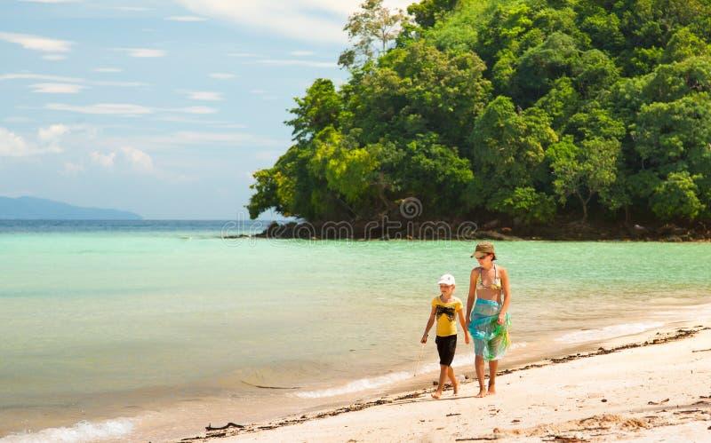 Mamá con su hija que viene a lo largo de la playa imágenes de archivo libres de regalías