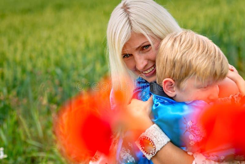 Mamá con su hijo en un prado magnífico El muchacho abraza a su madre firmemente y cariñosamente imagenes de archivo