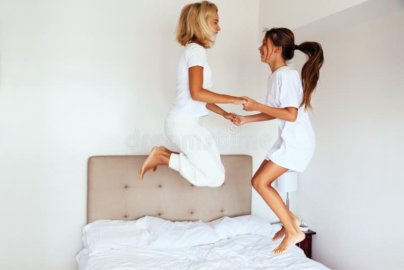 Mamá con su niño del preadolescente que salta en cama foto de archivo