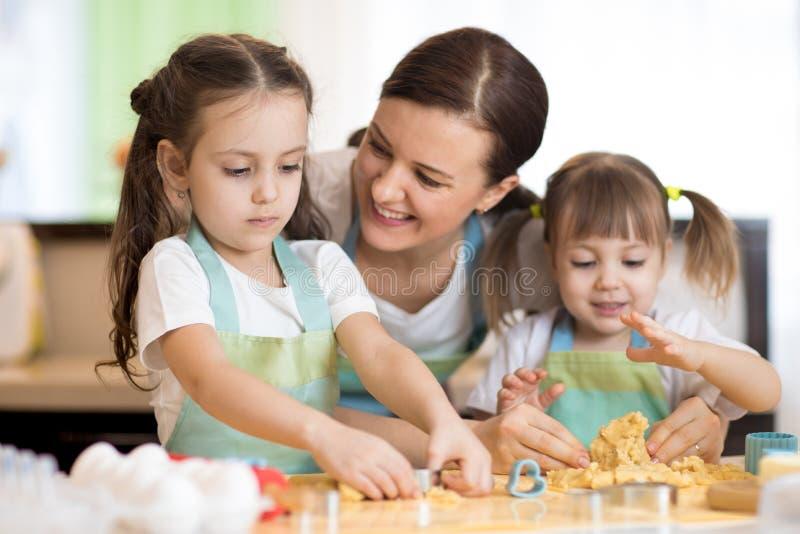 Mamá con sus hijas pequeñas está cocinando pastel de vacaciones en la cocina fotografía de archivo libre de regalías