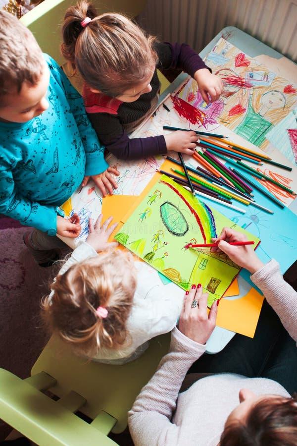 Mamá con sus pequeños hijas e hijo junto que dibujan un colorfu imágenes de archivo libres de regalías