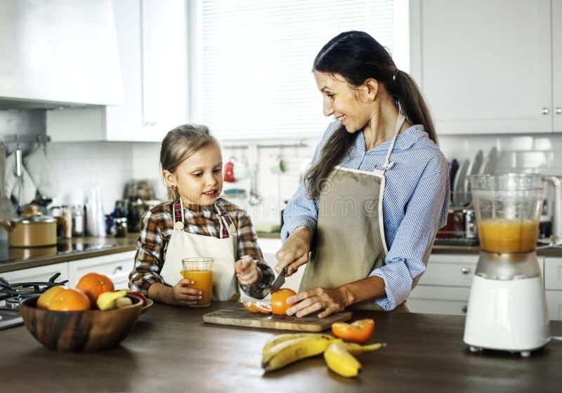 Mamá de ayuda de la hija en la preparación de la comida imagen de archivo
