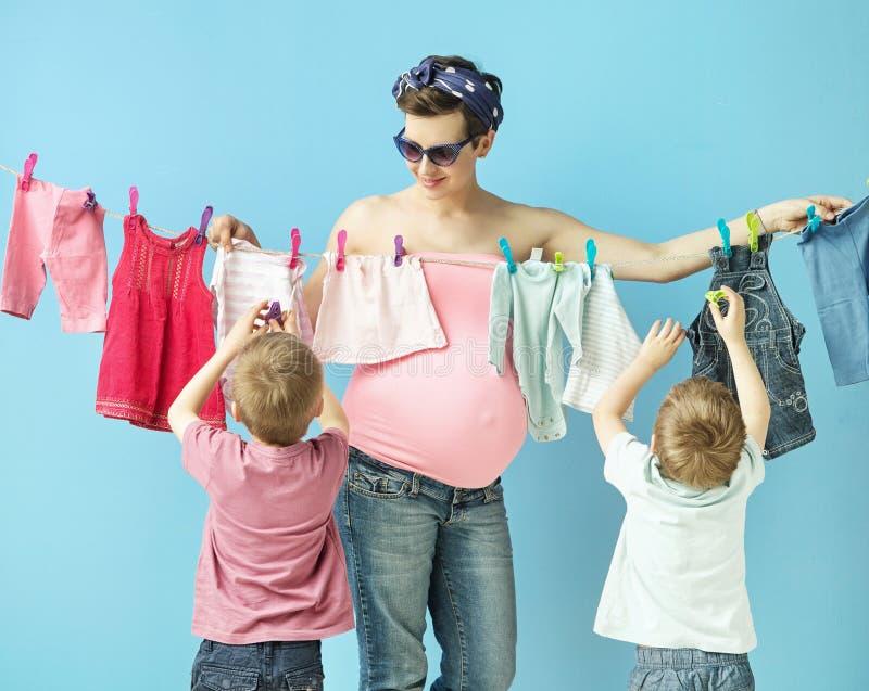 Mamá doiing el lavadero con sus hijos imagen de archivo libre de regalías