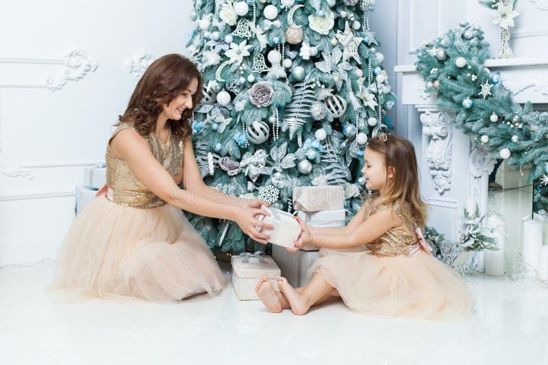 Mamá e hija felices debajo del árbol de navidad fotografía de archivo