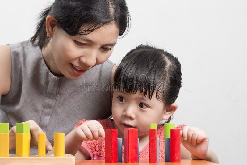 Mamá e hija que juegan el bloque de madera para crear una fantasía imagenes de archivo