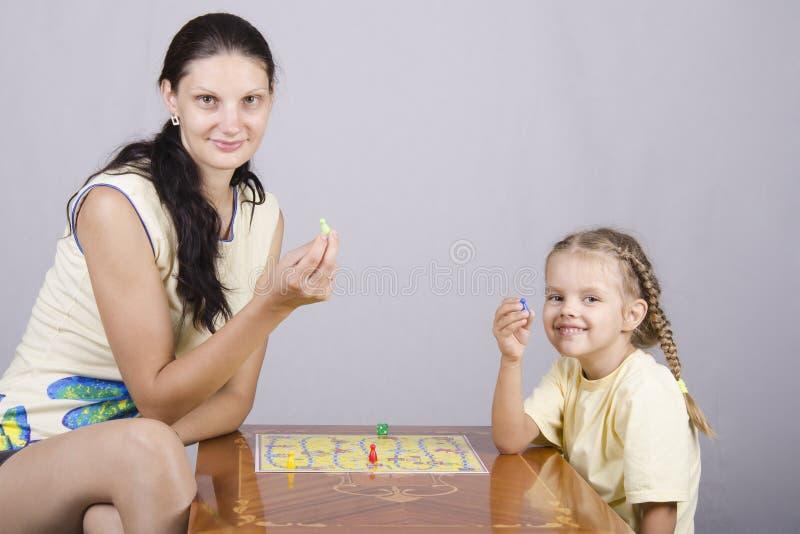 Mamá e hija que juegan a un juego de mesa imagen de archivo