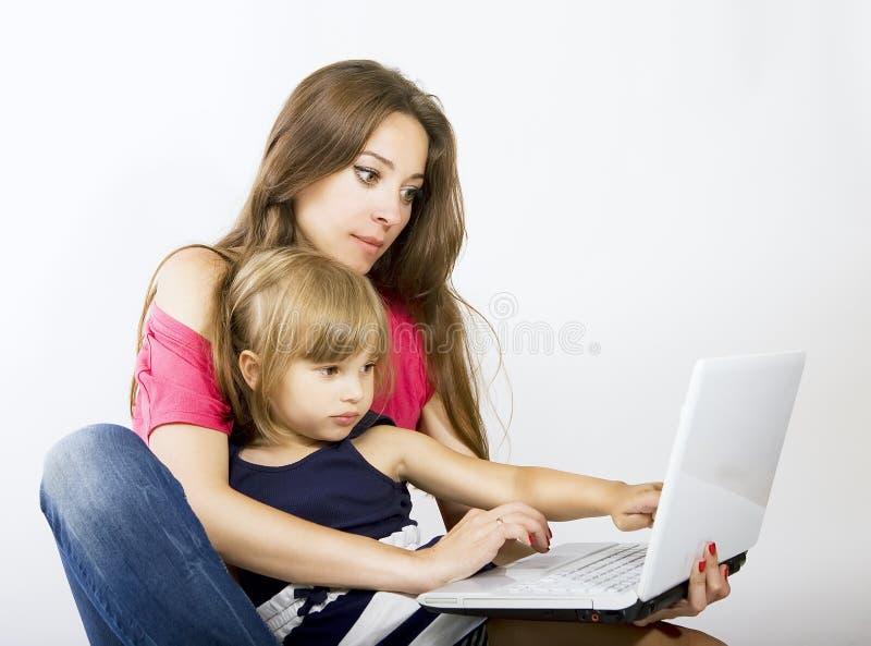 Mamá e hija que trabajan en el ordenador portátil imagenes de archivo