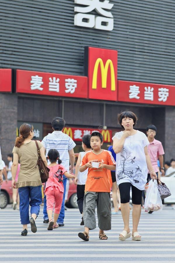Mamá e hijo en un paso de cebra con el mercado de MacDonald en fondo, Xiang Yang, China fotografía de archivo