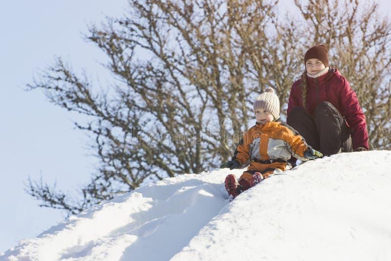 Mamá e hijo que bajan una diapositiva de la nieve Día de invierno imágenes de archivo libres de regalías