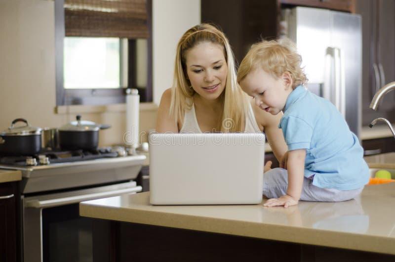 Mamá e hijo que usa un ordenador portátil imágenes de archivo libres de regalías