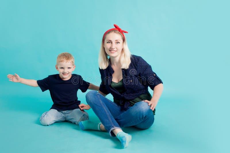Mamá e hijos, retrato en fondo azul imagenes de archivo