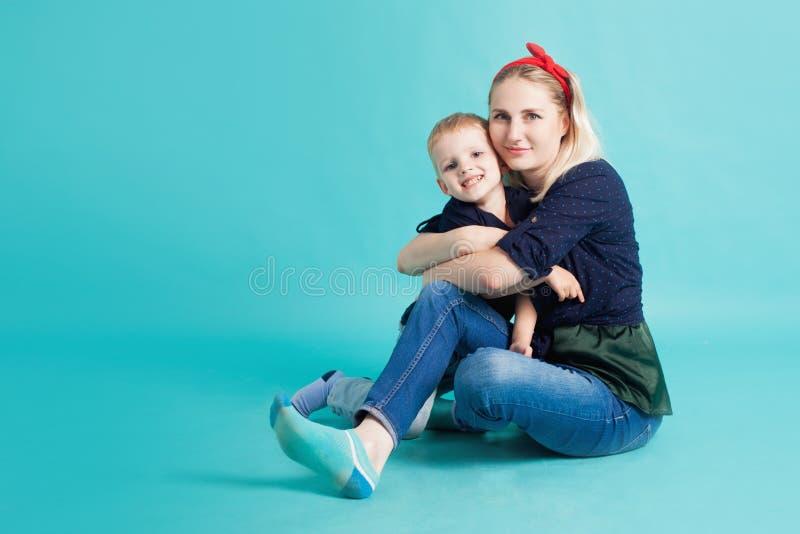 Mamá e hijos, retrato en fondo azul imagen de archivo libre de regalías