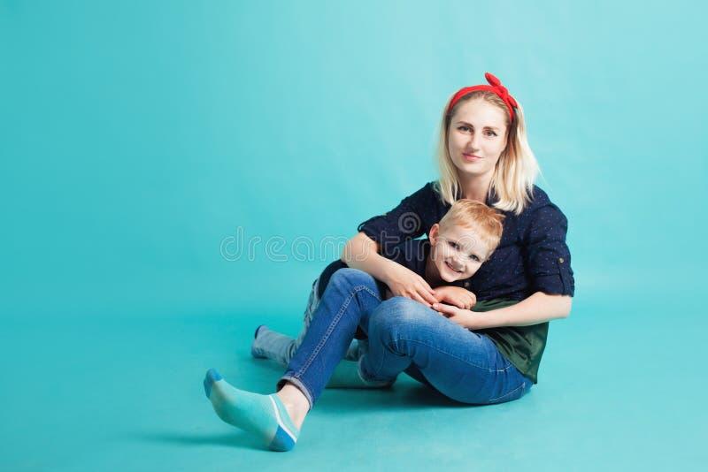 Mamá e hijos, retrato en fondo azul imágenes de archivo libres de regalías