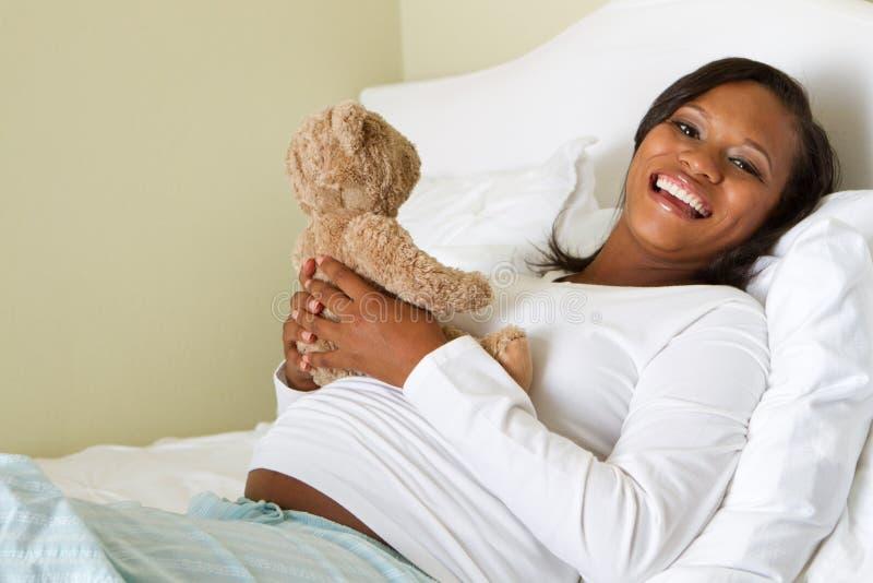 Mamá embarazada de los jóvenes que sostiene un oso de peluche imagenes de archivo