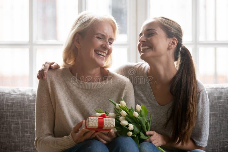 Mamá envejecida media feliz e hija adulta que celebran día de la madre imagen de archivo