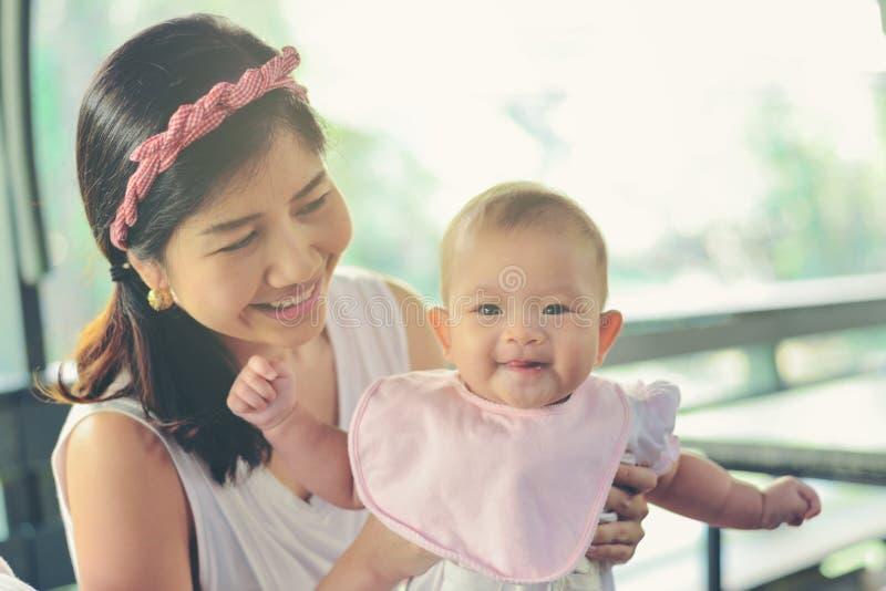 Mamá feliz asiática que detiene al bebé feliz Efectos del vintage, f suave imagenes de archivo